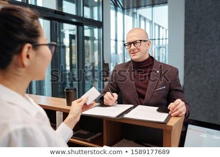 Calvo empresario pluma mirando femenino recepcionista Foto stock © pressmaster