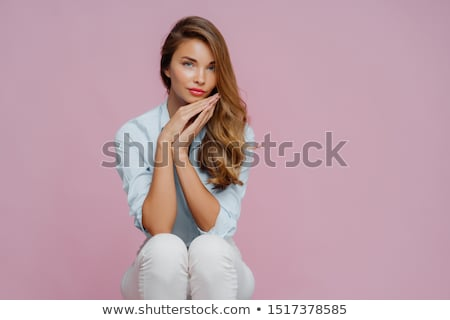 Serious beautiful woman with long hair, dressed in shirt and trousers, keeps palms pressed together  Stock photo © vkstudio