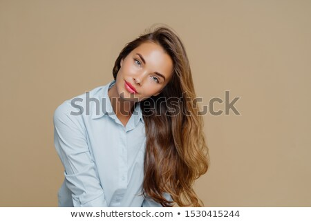 Portrait of pleasant looking female tilts head on right, has long well cared hair, wears blue shirt, Stock photo © vkstudio