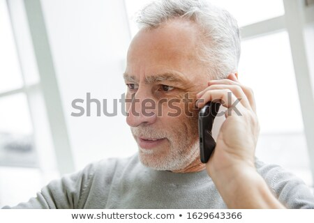 Photo closeup of serious mature man talking on cellphone Stock photo © deandrobot