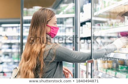Stock photo: Woman in supermarket shopping in dairy isle during lockdown