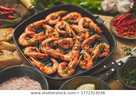 Tasty appetizing roasted shrimps prawns with spices on pan with ingredients on rusty background Stock photo © dash