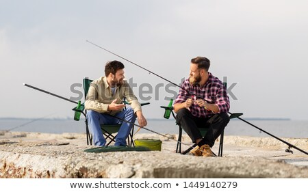 friends adjusting fishing rods with bait on pier Stock photo © dolgachov