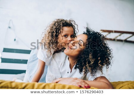 Curly toddler girl in bed, looking into camera  Stock photo © dacasdo