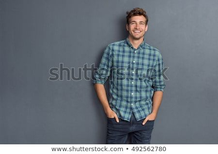 young fashion man leaning on a grey wall  Stock photo © feedough