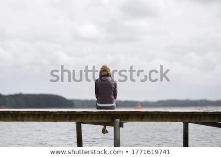 Genç bayan oturma ayaklar serin göl Stok fotoğraf © Klinker