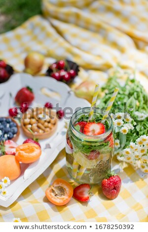 Lemonade with cherry, pear and lemon on the garden picnic Stock photo © dashapetrenko