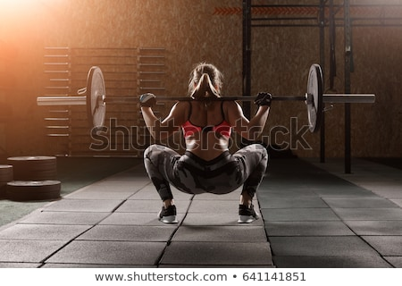 Portrait of a young fitness girl doing exercises with barbell Stock photo © deandrobot
