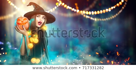 Beautiful young woman in black witch halloween costume with hat Stock photo © deandrobot