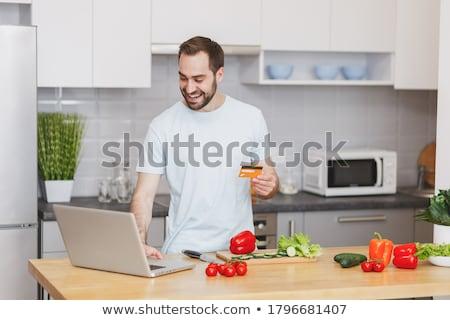 fiatalember · tart · számítógép · mosolyog · laptop · számítógép · gépel - stock fotó © nyul