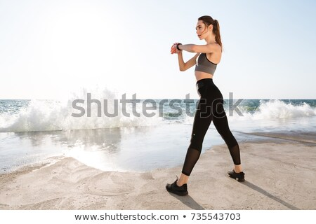 Full-length photo of young sport woman with perfect body checkin Stock photo © deandrobot