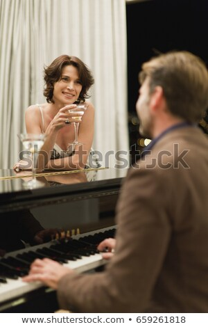 man playing piano for girlfriend at home stock photo © is2