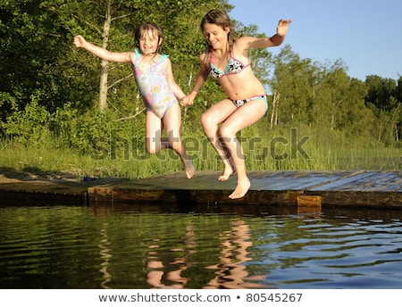 Teenage girls jumping into lake Stock photo © IS2