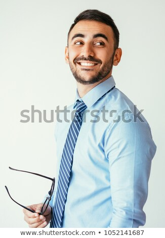 handsome young businessman looking to side on grey background stock photo © feedough