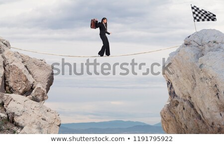 Business concept of businesswoman who overcome the problems reaching the flag on a rope Stock photo © alphaspirit