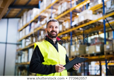 warehouse worker with clipboard in safety vest stock photo © dolgachov