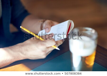 man with beer writing to notebook at bar or pub Stock photo © dolgachov