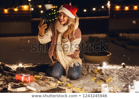 excited young woman sitting outdoors in evening in christmas hat take a selfie mobile phone stock photo © deandrobot