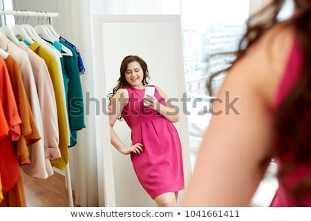 Stock photo: plus size woman taking at mirror selfie at home