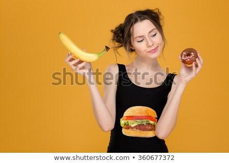 doubting woman with fruits looking at hamburger Stock photo © dolgachov