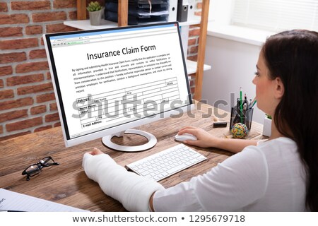 Stok fotoğraf: Businesswoman With Bandage Hand Filling Insurance Claim Form
