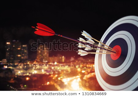 Arrow hit the center of target with modern skyline background. Business target achievement concept.  Stock photo © alphaspirit