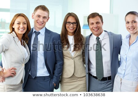 group of cheerful smart dressed friends standing stock photo © deandrobot