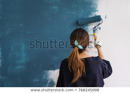 Smiling women painting the wall with roller Stock photo © Kzenon