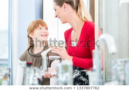 Happy mother looking with her daughter at two faucets in a sanitary ware shop Stock photo © Kzenon