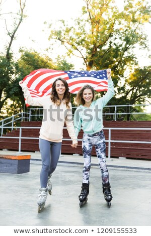 Friends sisters on rollers in park outdoors holding USA flag. Stock photo © deandrobot