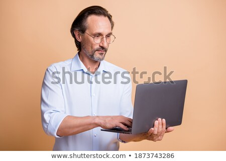 Happy guy in formalwear looking at computer screen Stock photo © pressmaster