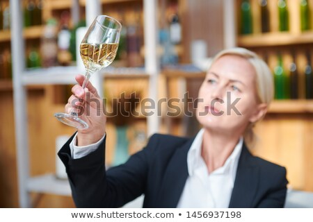 Female hand holding bokal woth white wine while examining its color Stock photo © pressmaster