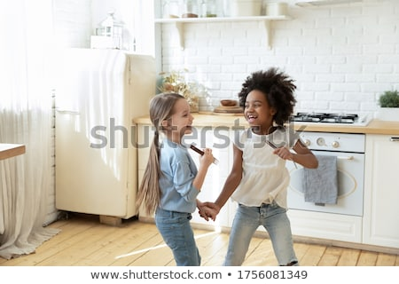 Two vivacious lively little girls jumping together Stock photo © Giulio_Fornasar