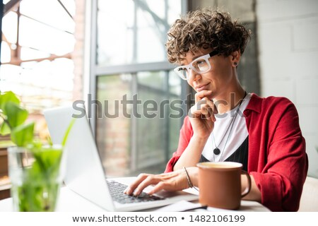 Stock photo: Busy young elegant woman in eyeglasses looking at laptop display