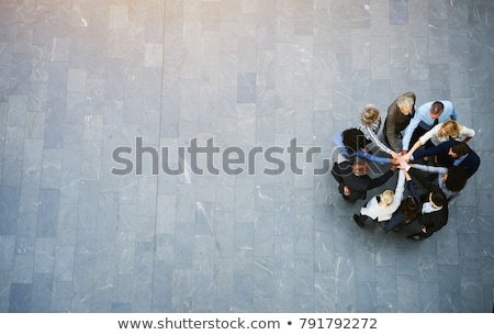Team of diverse business people stacking their hands together Stock photo © Kzenon
