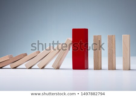 Red Wooden Block Amidst Falling And Upright Domino Pieces Stock photo © AndreyPopov