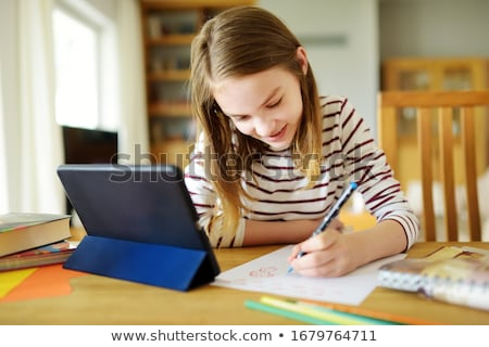 student girl with tablet computer doing homework stock photo © dolgachov