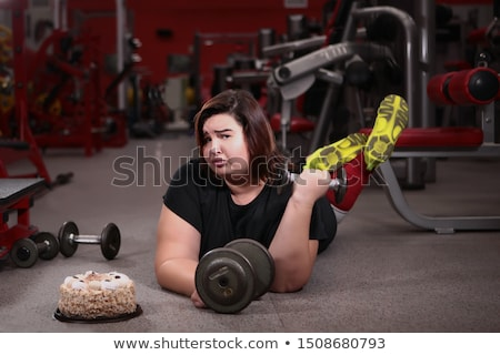 Young woman wanting to lose weight is engaged in the gym Stock photo © galitskaya