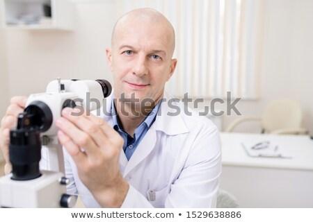 łysy w średnim wieku okulista posiedzenia kamery pracy Zdjęcia stock © pressmaster