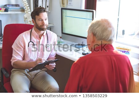 High angle view of a Caucasian male doctor talking to Caucasian senior patient while holding medical Stock photo © wavebreak_media