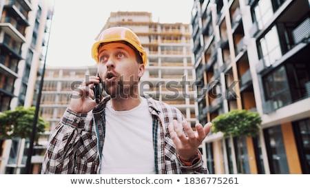 Negatywne młody człowiek budowniczy mówić telefonu komórkowego Fotografia Zdjęcia stock © deandrobot