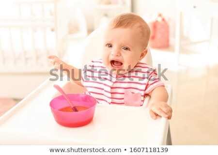 Stock photo: Little baby girl crying on a high chair