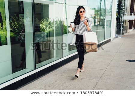 Woman leaving a store with shopping bags Stock photo © photography33