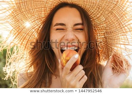 kadın · yeme · şeftali · güzel · bir · kadın · bakıyor · yan - stok fotoğraf © feedough