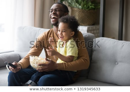 Stock photo: Cute Friends lounging on a sofa watching a movie in living room