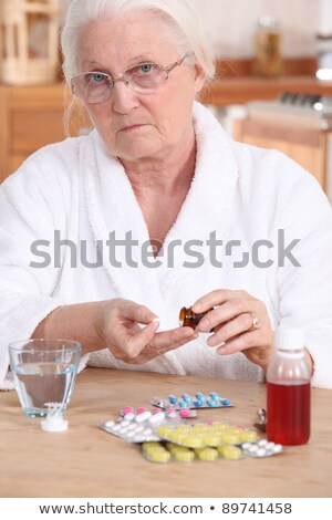 Unhappy senior citizen taking her medication Stock photo © photography33