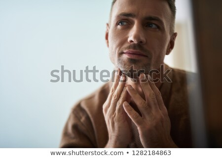 casual man touches his unshaven chin Stock photo © feedough