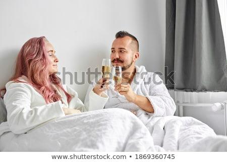 romantic couple cuddling bed champagne celebrating stock photo © candyboxphoto