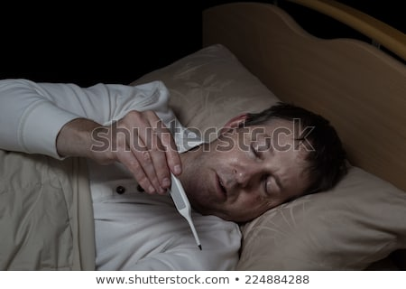 Mature man with high fever in bed  Stock photo © tab62