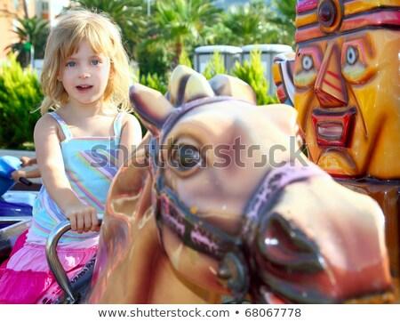 blond girl with fairground horse enjoy in park stock photo © lunamarina